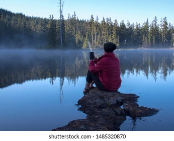 Older woman wearing a red jacket and black hat holding a coffee cup sitting on rocks at the edge of a lake.