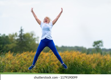 Older woman wearing workout outfit jumping for joy with arms and legs spread in midair in front of blurry yellow flowers