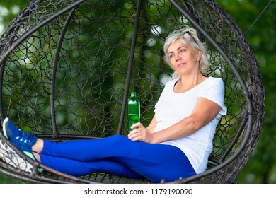 Older woman with white hair holding green liquor bottle while sitting in metal wire nest and blurry tree in background