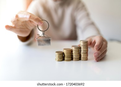 older woman with white hair and money on her hands in her home on a sunny day
