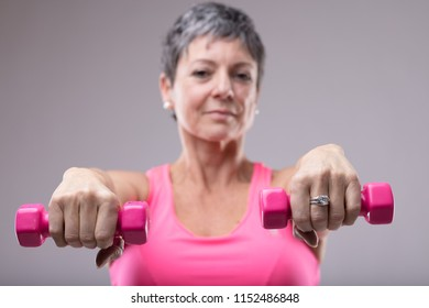 Older woman working out with a pair of colorful pink dumbbells holding them extended to the camera with focus to the weights in a health and fitness concept