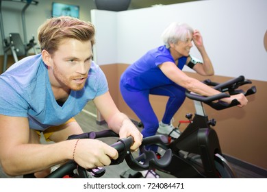 older woman and young man doing bike in gym