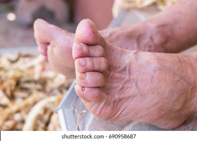 older woman's foot near some dried beans