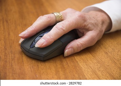 Older woman's hand using a wireless computer mouse. Focus is on the front of the mouse / end of the fingers.