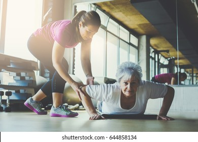 Older women doing pushups. Young personal trainer helping senior woman. Workout in rehabilitation center.