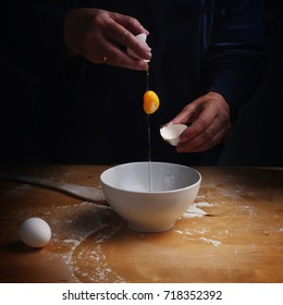 older women hands breaking an egg with falling egg yolk over a bowl, wooden kitchen board, dark background with copy space, selected focus
