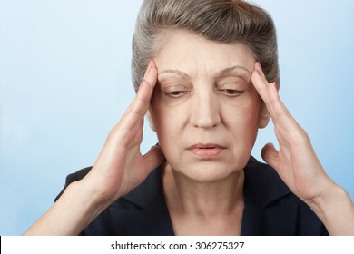 Older women have a headache and she holds her hands at the temples