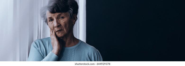 Older women suffering from depression standing lonely in dark room
