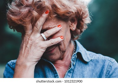 Older women worrying with her hands over her face