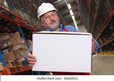 older worker in uniform and hardhat carrying box in warehouse