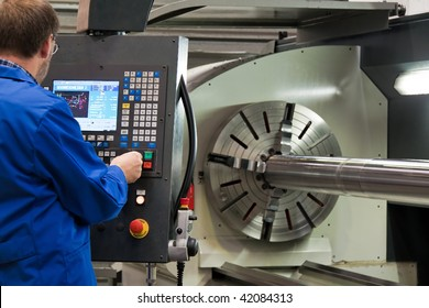 An older workers in the metal industry with CNC milling machine.