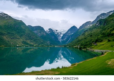Oldevatnet fjord and view to the rocks of Briksdalsbreen glacier. National touristic route of Norway.