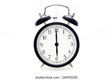 Oldfashioned black glossy alarm clock showing 6 o'clock