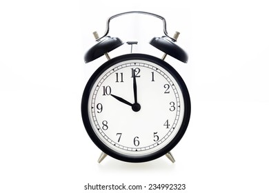 Oldfashioned black glossy alarm clock showing 10 o'clock