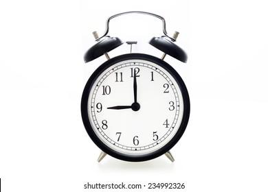 Oldfashioned black glossy alarm clock showing 9 o'clock