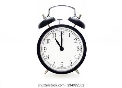 Oldfashioned black glossy alarm clock showing 11 o'clock