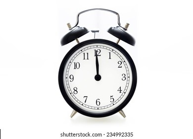 Oldfashioned black glossy alarm clock showing 12 o'clock