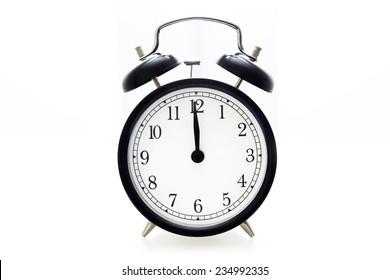 Oldfashioned black glossy alarm clock showing 12 o'clock
