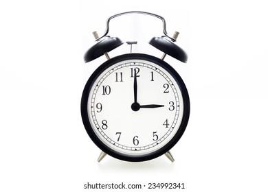 Oldfashioned black glossy alarm clock showing 3 o'clock