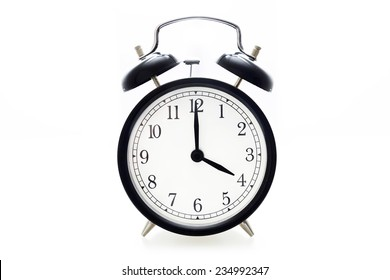 Oldfashioned black glossy alarm clock showing 4 o'clock