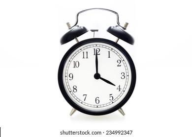 Oldfashioned black glossy alarm clock showing 4 o'clock