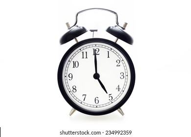 Oldfashioned black glossy alarm clock showing 5 o'clock