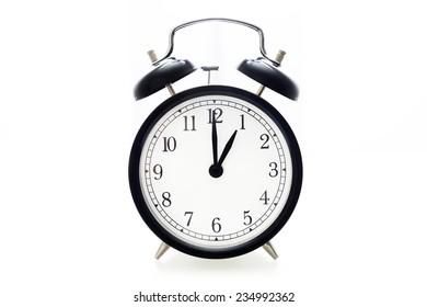 Oldfashioned black glossy alarm clock showing 1 o'clock