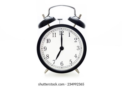 Oldfashioned black glossy alarm clock showing 7 o'clock
