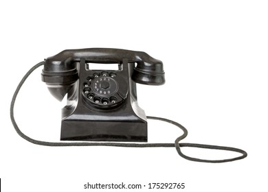 Old-fashioned black rotary telephone instrument with its handset on the cradle on a white background with a reflection and copyspace