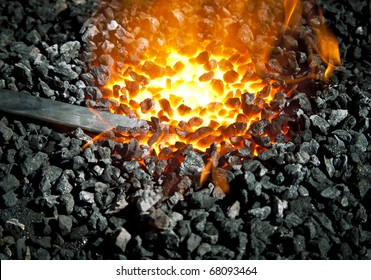 Old-fashioned blacksmith furnace with burning coals (focus is on the iron)