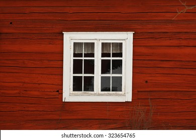 Old-fashioned cottage painted in swedish traditional red color with a white window..