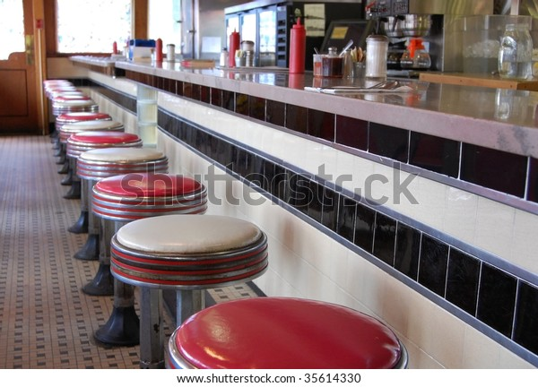 An old-fashioned diner with a tile floor and art deco style bar stools.