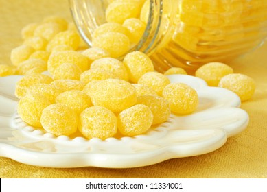 Old-fashioned lemon drop candies in a decorative dish with vintage jar in the background.  Close-up with shallow dof.