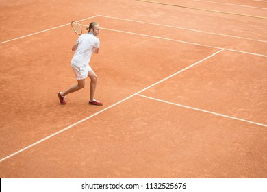 old-fashioned male tennis player with racket on brown tennis court