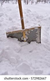 An old-fashioned metal shovel for snow removal with wooden handle.