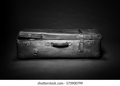 Old-fashioned old damaged suitcase in studio on dark grey background