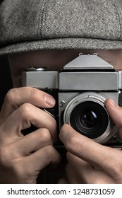 Old-fashioned Photographer. Close-up portrait of a photographer photo-shooting by vintage film camera.