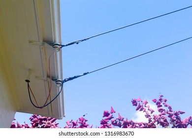 Old-fashioned power lines providing electricty access via insulator to surfiet of house close-up