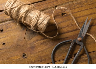 Old-fashioned scissors cutting piece of garden twine on brown wooden  background.
