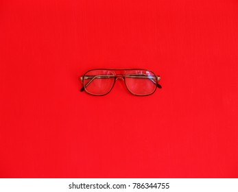 Old-fashioned shell-framed eye glasses against a red wall. Minimal photography in monochrome.
