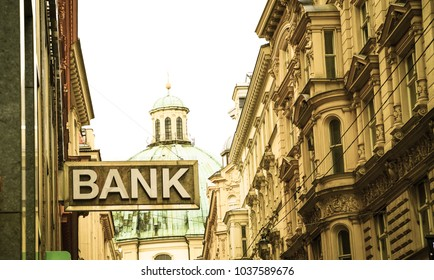 Old-fashioned style image simple bank sign in narrow Vienna street surrounded by traditional European architecture with green dome of St Peter's basilica behind