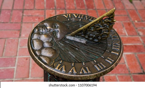 An old-fashioned sundial with a sun face in a park.