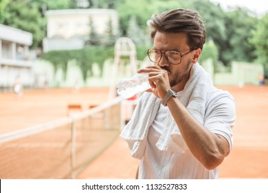 old-fashioned tennis player with towel drinking water after training on tennis court