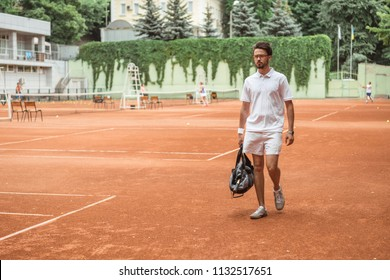 old-fashioned tennis player walking with bag after training on tennis court