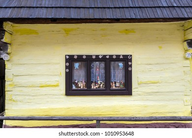 Old-fashioned window of wooden house on yellow wall in Vlkolinec