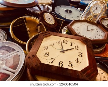 Old-fasioned clocks.  Vintage of wall clocks and table clocks. Pile up of aged clocks on the floor.