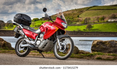 Oldham, UK, April 29, 2015: Red Honda Transalp XLV650 motorbike with countryside background