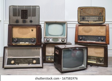 oldie things. radios, tvs, camera, and frame on wooden floor