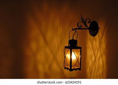 Old-looking lantern with incandescent lightbulb throwing shadow on corner wall