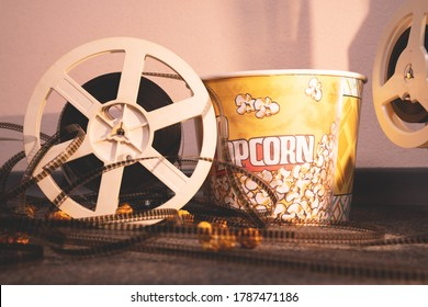 Old-school projector reel with uncoiled film is leaning against paper bucket of caramel popcorn in side warm light of lamp, front view. Traditional attributes of watching movies.